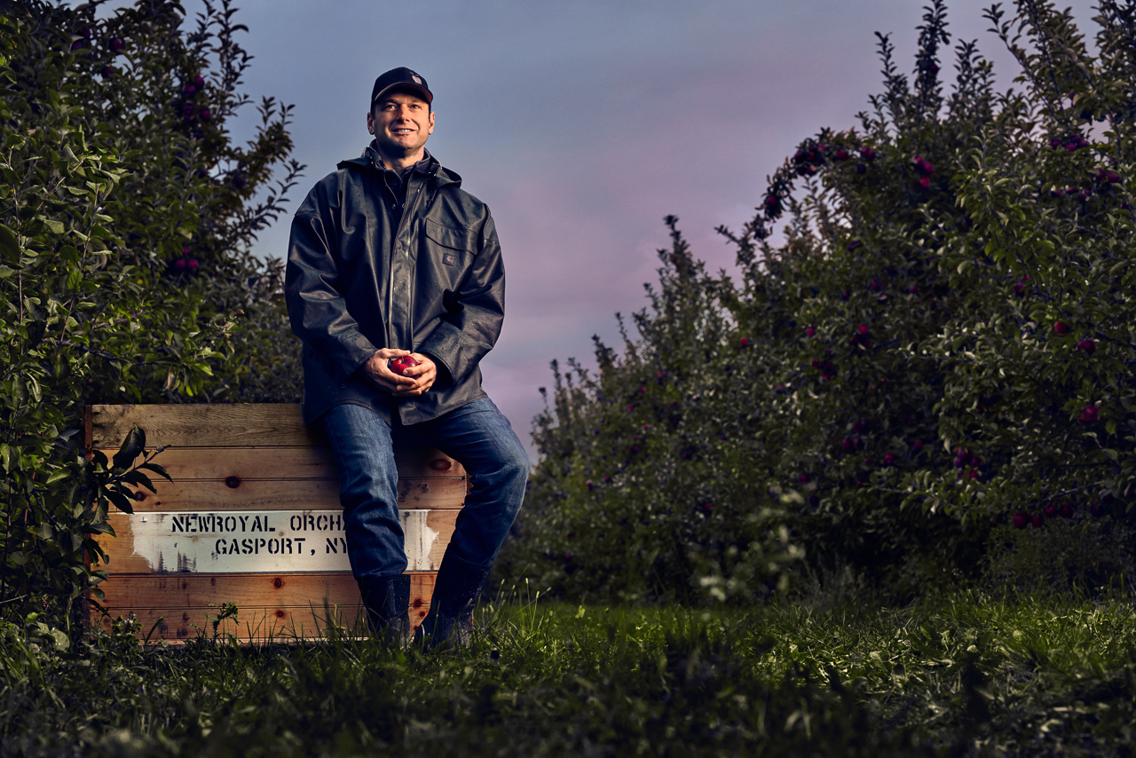 Garett Mayer sitting on an apple crate at New Royal Orchards in Gasport NY at sunrise. Garett is the 5th generation owner of Mayer Brothers Cider Mill in the Western NY town of West Seneca. Garett, The 165 year old cider press, and surrounding orchards were photographed as part of a success stories campaign for M&T Bank, with which Mayer Brothers has been doing business for 90+ years.