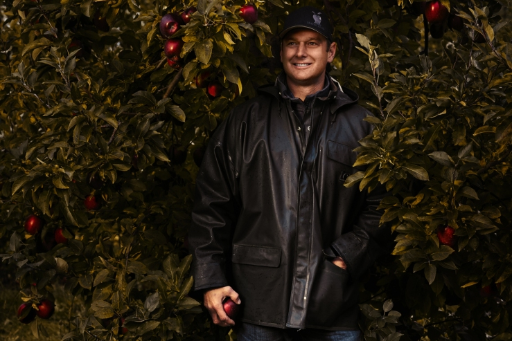 Garett Mayer standing amongst apples and trees at Royal Orchards. Garett is the 5th generation owner of Mayer Brothers Cider Mill in the Western NY town of West Seneca. Garett, The 165 year old cider press, and surrounding orchards were photographed as part of a success stories campaign for M&T Bank, with which Mayer Brothers has been doing business for 90+ years.