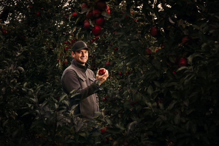 Garett Mayer holding an apple amongst the trees at New Royal Orchards in Gasport NY. Garett is the 5th generation owner of Mayer Brothers Cider Mill in the Western NY town of West Seneca. Garett, The 165 year old cider press, and surrounding orchards were photographed as part of a success stories campaign for M&T Bank, with which Mayer Brothers has been doing business for 90+ years.