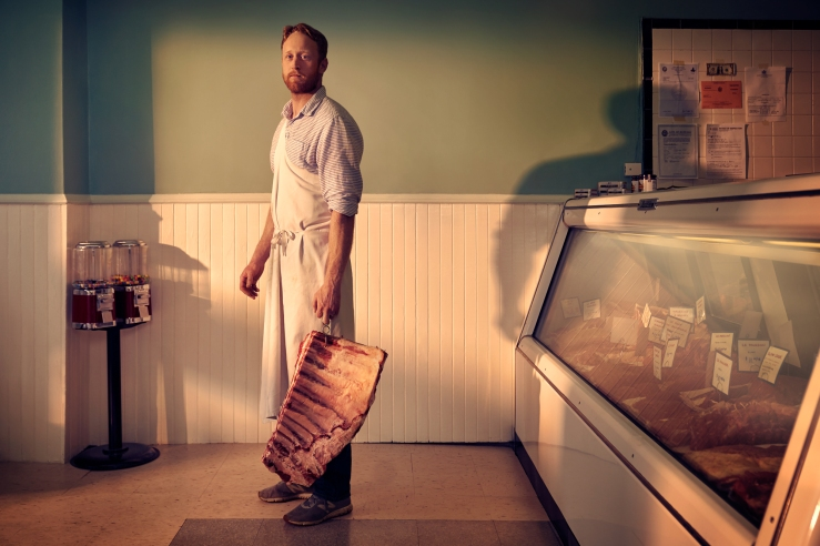 Moriarty Meats owner Tom Moriarty standing in the early morning sun with a rack of beef ribs.